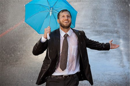 people with umbrellas in the rain - Enthusiastic businessman with tiny umbrella in rainy street Stock Photo - Premium Royalty-Free, Code: 6113-06899670