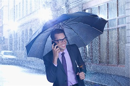 people with umbrellas in the rain - Happy businessman talking on cell phone under umbrella in rainy street Stock Photo - Premium Royalty-Free, Code: 6113-06899677