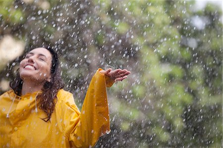 Happy woman standing with arms outstretched in rain Stock Photo - Premium Royalty-Free, Code: 6113-06899602