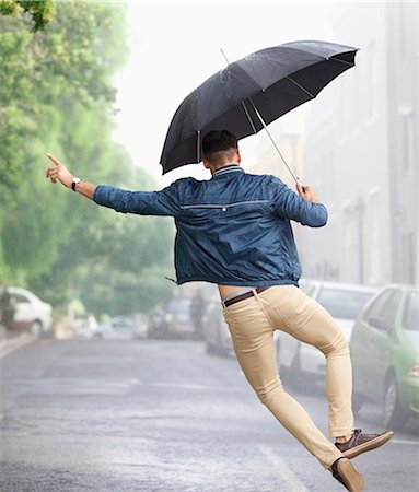 people with umbrellas in the rain - Man dancing with umbrella in rainy street Stock Photo - Premium Royalty-Free, Code: 6113-06899609