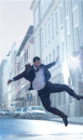 Businessman dancing in rainy street Stock Photo - Premium Royalty-Free, Code: 6113-06899612