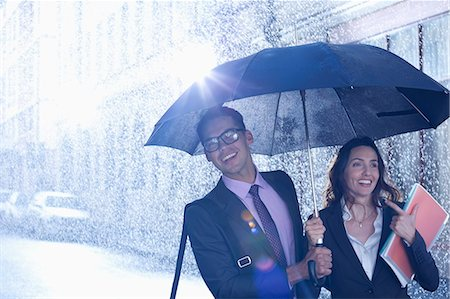 people with umbrellas in the rain - Happy businessman and businesswoman walking under umbrella in rain Stock Photo - Premium Royalty-Free, Code: 6113-06899614