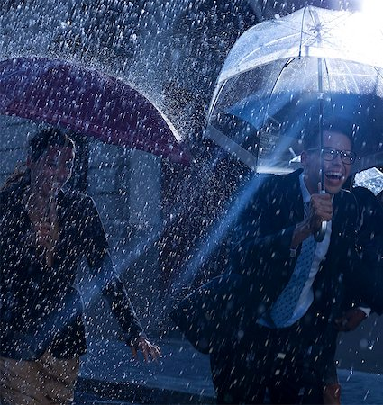 Happy business people running with umbrellas in rain Stock Photo - Premium Royalty-Free, Code: 6113-06899615