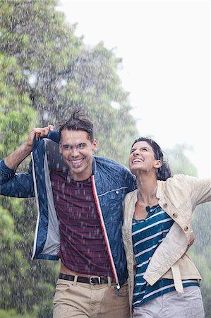Happy couple walking in rain Stock Photo - Premium Royalty-Free, Code: 6113-06899620