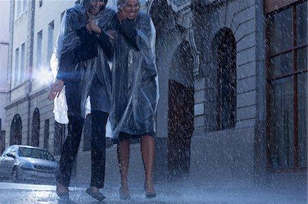 Businesswomen in ponchos walking in rainy street Stock Photo - Premium Royalty-Free, Code: 6113-06899624
