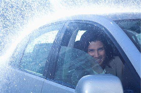 Portrait of smiling businesswoman inside car in rain Stock Photo - Premium Royalty-Free, Code: 6113-06899626