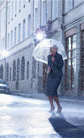 Businesswoman under umbrella in rainy street Stock Photo - Premium Royalty-Free, Code: 6113-06899634