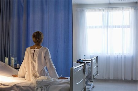 Patient wearing gown on hospital bed Stock Photo - Premium Royalty-Free, Code: 6113-06908243