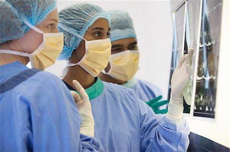 Surgeons examining x-rays in operating room Stock Photo - Premium Royalty-Free, Code: 6113-06908245