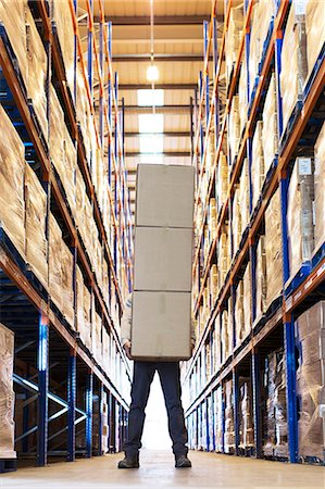Worker holding boxes in warehouse Stock Photo - Premium Royalty-Free, Code: 6113-06908391