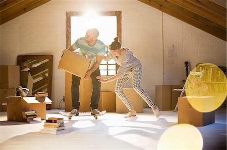Couple unpacking boxes in attic Stock Photo - Premium Royalty-Free, Code: 6113-06908497