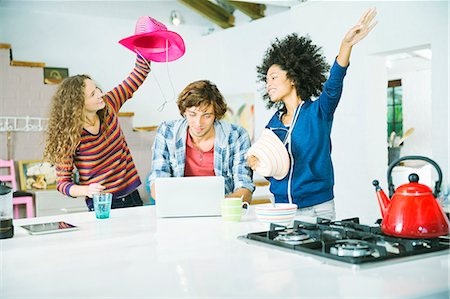Friends playing in kitchen Stock Photo - Premium Royalty-Free, Code: 6113-06908498