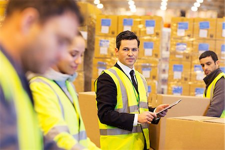 supervising - Businessman and workers in warehouse Stock Photo - Premium Royalty-Free, Code: 6113-06908402