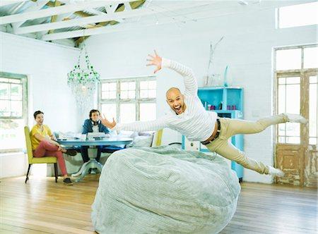 Man jumping into beanbag chair Stock Photo - Premium Royalty-Free, Code: 6113-06908572
