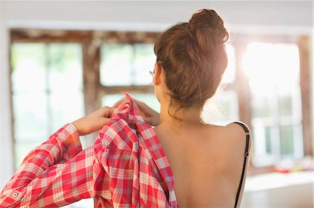 Woman putting on shirt in bedroom Stock Photo - Premium Royalty-Free, Code: 6113-06908588