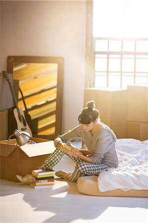 Woman unpacking box in new home Stock Photo - Premium Royalty-Free, Code: 6113-06908523