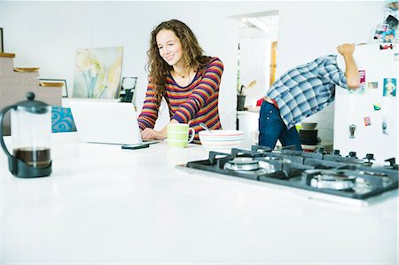 fridge - Woman using laptop at breakfast Stock Photo - Premium Royalty-Free, Code: 6113-06908522