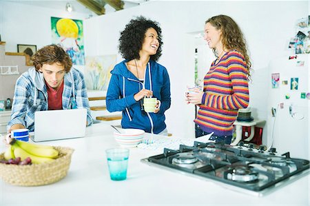 Friends relaxing together in kitchen Stock Photo - Premium Royalty-Free, Code: 6113-06908524