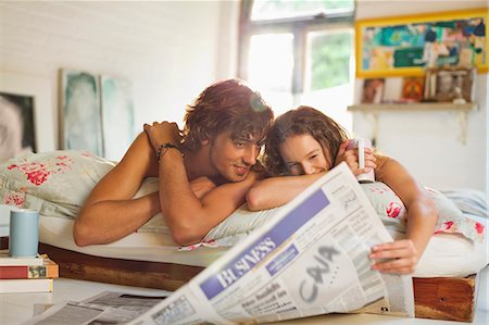 Couple reading newspaper together in bed Stock Photo - Premium Royalty-Free, Code: 6113-06908533