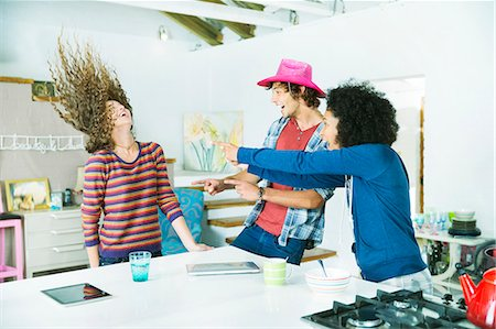 Friends playing together in kitchen Stock Photo - Premium Royalty-Free, Code: 6113-06908643