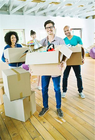 Friends unpacking boxes in new home Stock Photo - Premium Royalty-Free, Code: 6113-06908665
