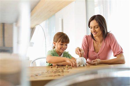 savings - Mother and daughter filling piggy bank Stock Photo - Premium Royalty-Free, Code: 6113-06908678