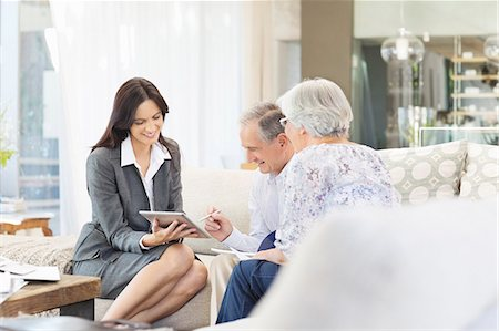 Financial advisor using tablet computer with clients Stock Photo - Premium Royalty-Free, Code: 6113-06908687