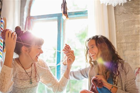 Women playing with yarn together Stock Photo - Premium Royalty-Free, Code: 6113-06908601