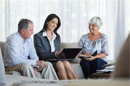 finance - Financial advisor talking to couple on sofa Stock Photo - Premium Royalty-Free, Code: 6113-06908762