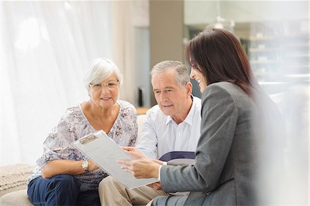 Financial advisor talking to couple on sofa Stock Photo - Premium Royalty-Free, Code: 6113-06908713