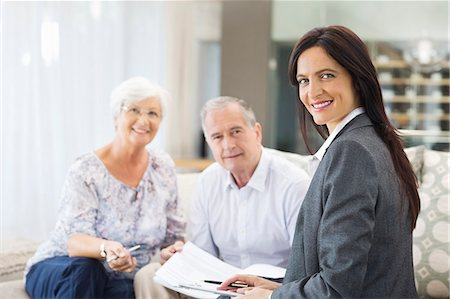 Financial advisor talking to couple on sofa Stock Photo - Premium Royalty-Free, Code: 6113-06908718
