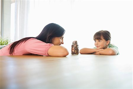 Mother and daughter with change jar Stock Photo - Premium Royalty-Free, Code: 6113-06908727