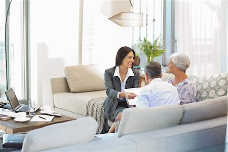 finance - Financial advisor talking to couple on sofa Stock Photo - Premium Royalty-Free, Code: 6113-06908725