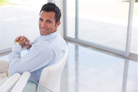 Businessman smiling in office chair Fotografie stock - Premium Royalty-Free, Codice: 6113-06908853