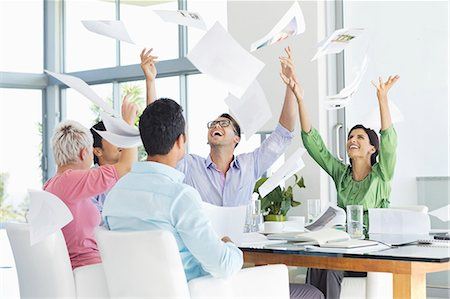 five people - Business people tossing papers in air in meeting Stock Photo - Premium Royalty-Free, Code: 6113-06908877