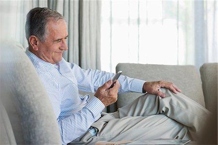 Older man using cell phone on sofa Stock Photo - Premium Royalty-Free, Code: 6113-06908809