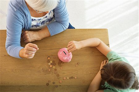 Older woman and granddaughter filling piggy bank Stock Photo - Premium Royalty-Free, Code: 6113-06908828