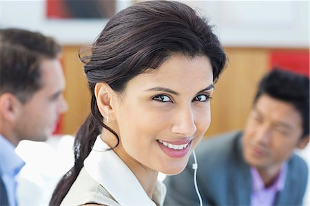 Businesswoman listening to headphones in office Stock Photo - Premium Royalty-Free, Code: 6113-06909055