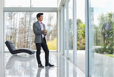 rich lifestyle - Businessman standing at office window Stock Photo - Premium Royalty-Free, Code: 6113-06909037