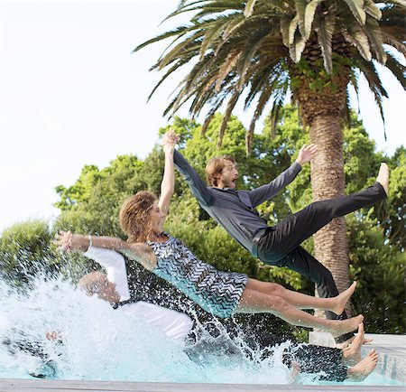 people falling - Friends jumping backwards into swimming pool Stock Photo - Premium Royalty-Free, Code: 6113-06909147