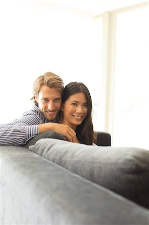 Smiling couple relaxing on sofa Stock Photo - Premium Royalty-Free, Code: 6113-06909270