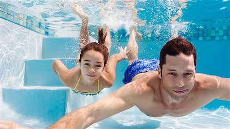Father and daughter swimming in pool Stock Photo - Premium Royalty-Free, Code: 6113-06909296