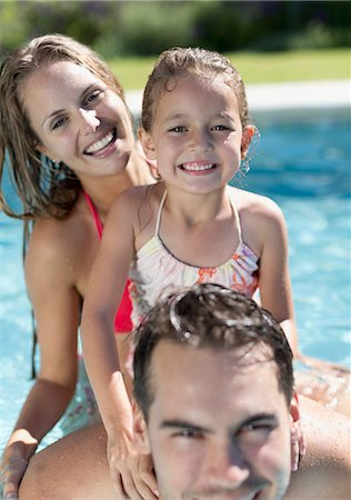 Family smiling in swimming pool Stock Photo - Premium Royalty-Free, Code: 6113-06909346