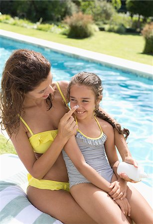 Mother applying sunscreen to daughter's nose Stock Photo - Premium Royalty-Free, Code: 6113-06909368
