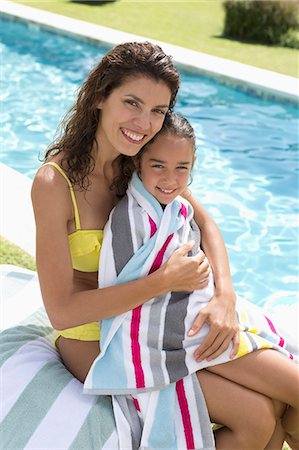 Mother and daughter relaxing by swimming pool Stock Photo - Premium Royalty-Free, Code: 6113-06909372