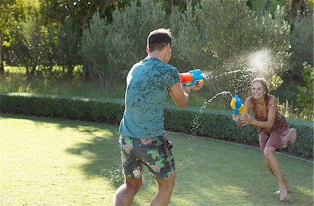 Couple playing with water guns in backyard Stock Photo - Premium Royalty-Free, Code: 6113-06909376