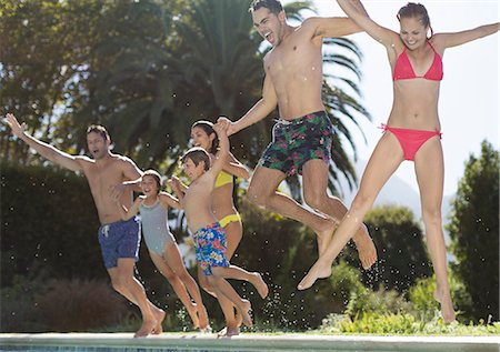 Family jumping into swimming pool Stock Photo - Premium Royalty-Free, Code: 6113-06909379