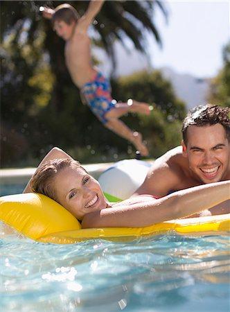 shirtless men - Family playing in swimming pool Stock Photo - Premium Royalty-Free, Code: 6113-06909381