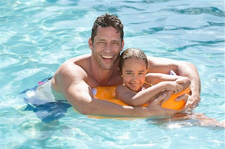 Father and daughter relaxing in swimming pool Stock Photo - Premium Royalty-Free, Code: 6113-06909387