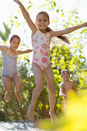 Children jumping on trampoline outdoors Stock Photo - Premium Royalty-Free, Code: 6113-06909389